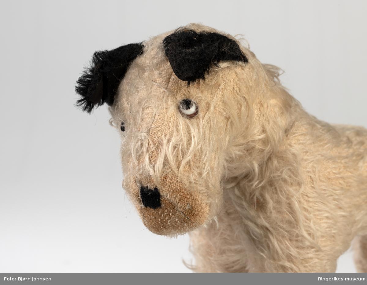 Fremstilling av hund i  liten størrelse, men med trekk fra en hund med ører, hale, poter og snute. Meltallkramper nederst på bakbena. Stoppet kropp. hodet kan dreies. Type terrierer. Stående.  Kosedyr for et barn.