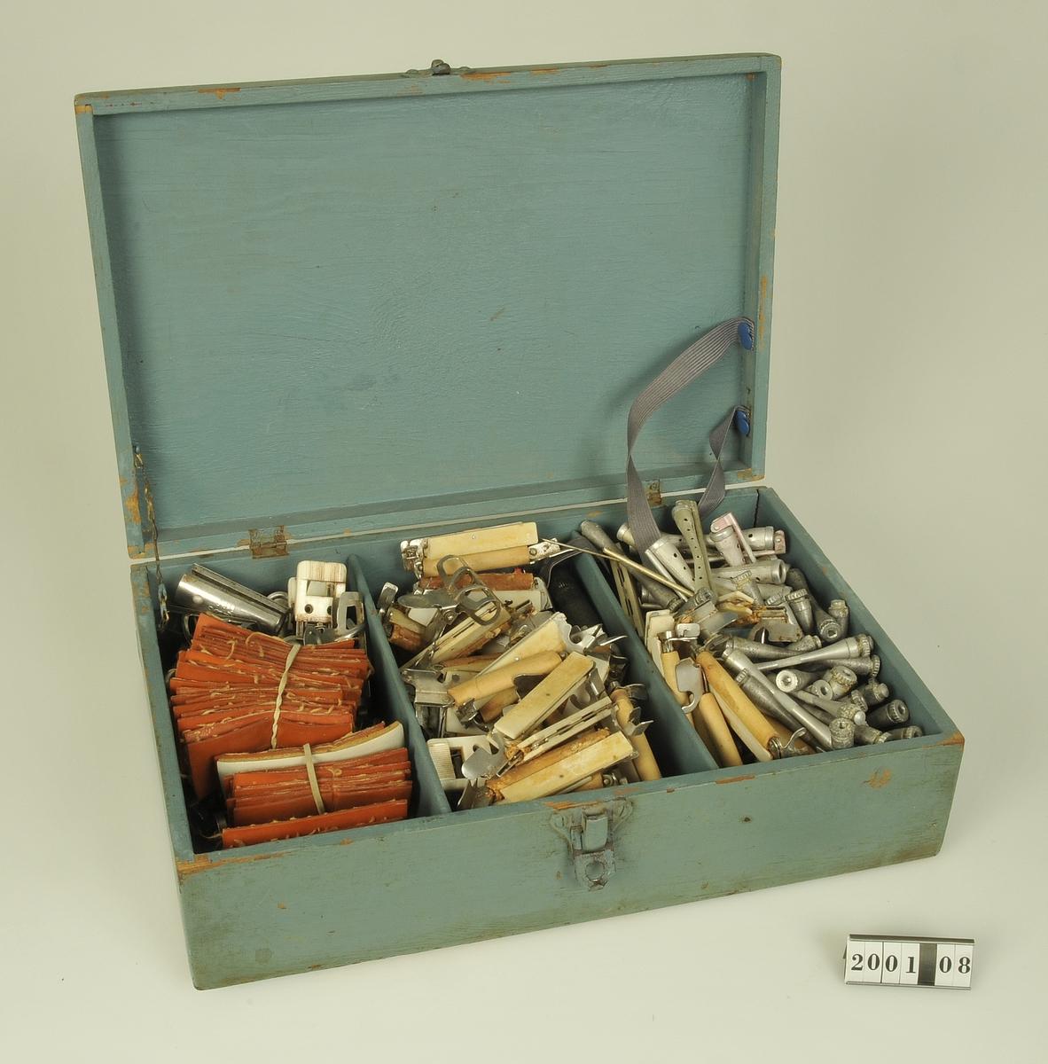 Grågrön trälåda som innehåller spolar, klämmor,plattor med mera som använts vid hårpermanent.