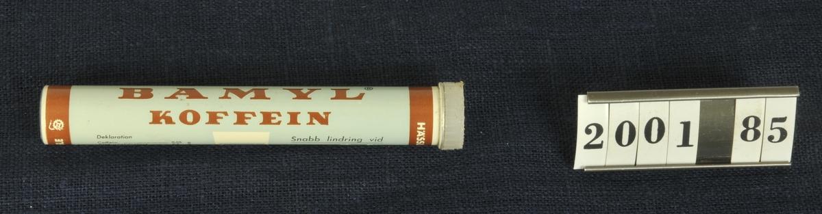 Grå och grön med vit text, med propp i plast. Har innehållit Bamyl koffein. Doseringsanvisningar och innehåll står på röret. 28 stämplat med rött i botten.