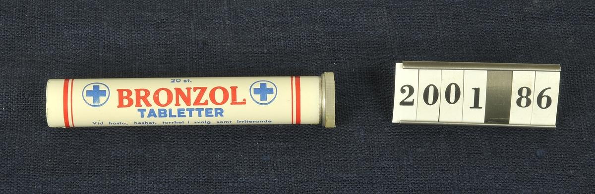 Vitt rör med text i blått och rött. Har innehållit 20 st Bronzol tabletter. Innehållsdeklaration står på röret.   En känd reklamslogan, till och med 1970-talet, för produkten löd: Hälsa för halsen - Bronzol!