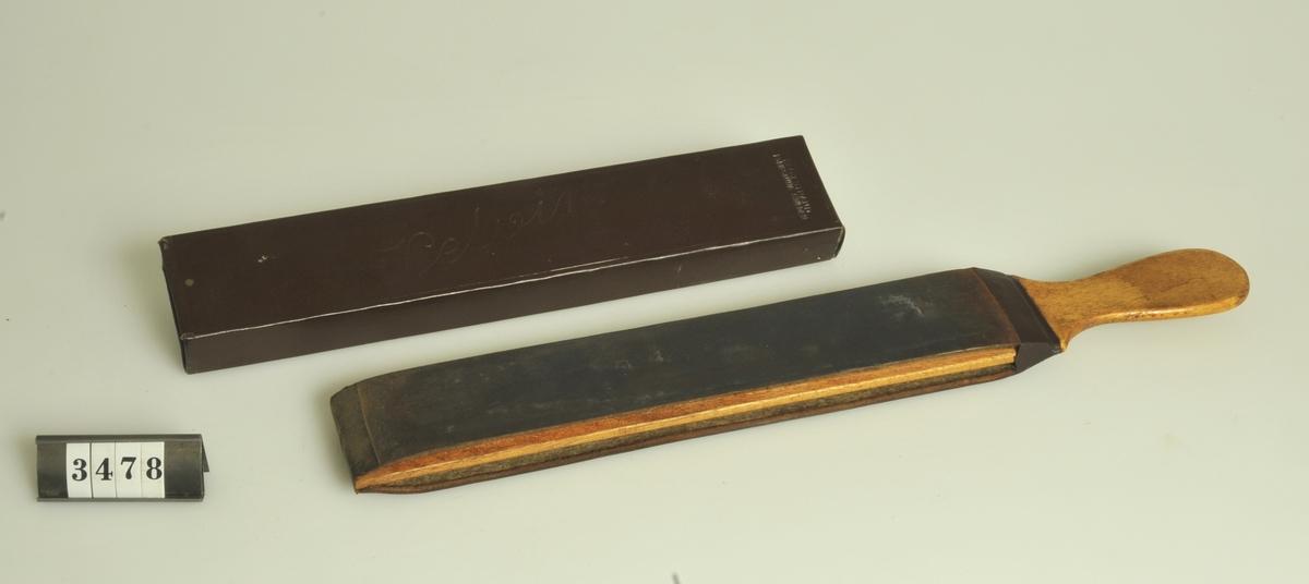Fodral: Av brun papp.  Längd: 25,5 cm. Bredd:   4,8 cm. Höjd:     2,2 cm.  Har använts i Fernbrings frisersalong, N. Strömgatan 24, Alingsås.
