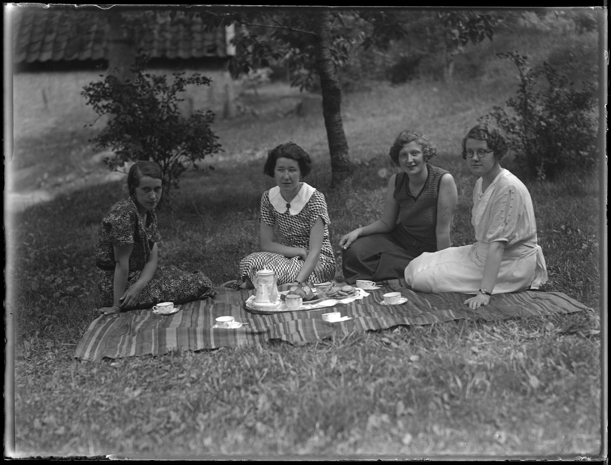"""Karin Helgesson, i mönstrad klänning längst ut på kanten, med vänner sitter på en picknickfilt. På filten är kaffekanna, koppar och kakor uppdukade. I fotografens anteckningar står det """"Karin Helgesson, Halö, med sällskap"""". Tolkat som Karin Sofia Helgesson."""