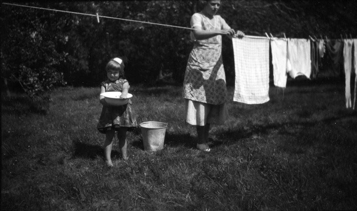 En kvinna och en flicka hänger tvätt på ett klädstreck, flickan håller i en balja.