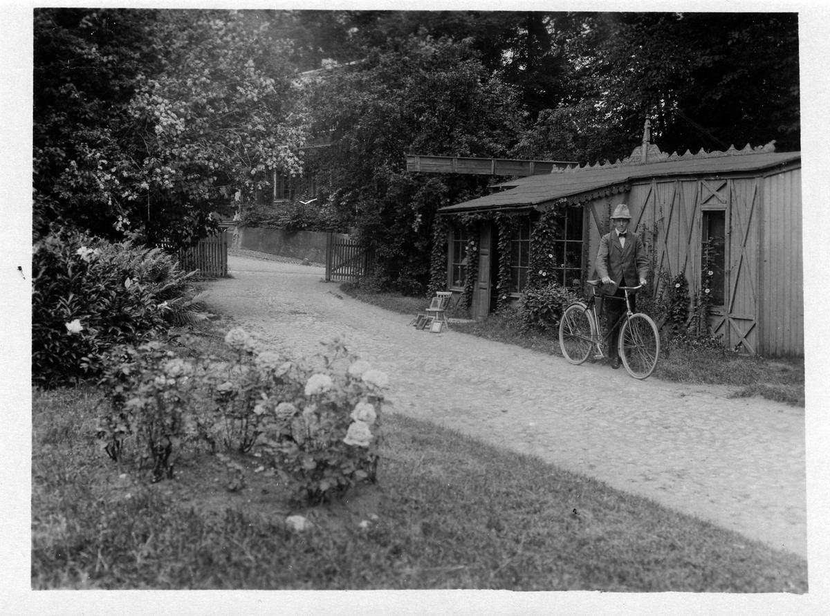 Man med cykel utanför Karin Möllers fotoateljé. Utanför ingången till ateljén pågår kontaktkopiering; ramar med negativ och så kallade utkopieringspapper eller dagsljuspapper har ställts i solen. När önskad svärta uppnåts togs pappret ur ramen, fixerades och sköljdes. Ateljén, som låg på bryggeritomten vid Lillån, övertog Möller efter fotograf Herman Hansen Scauw.
