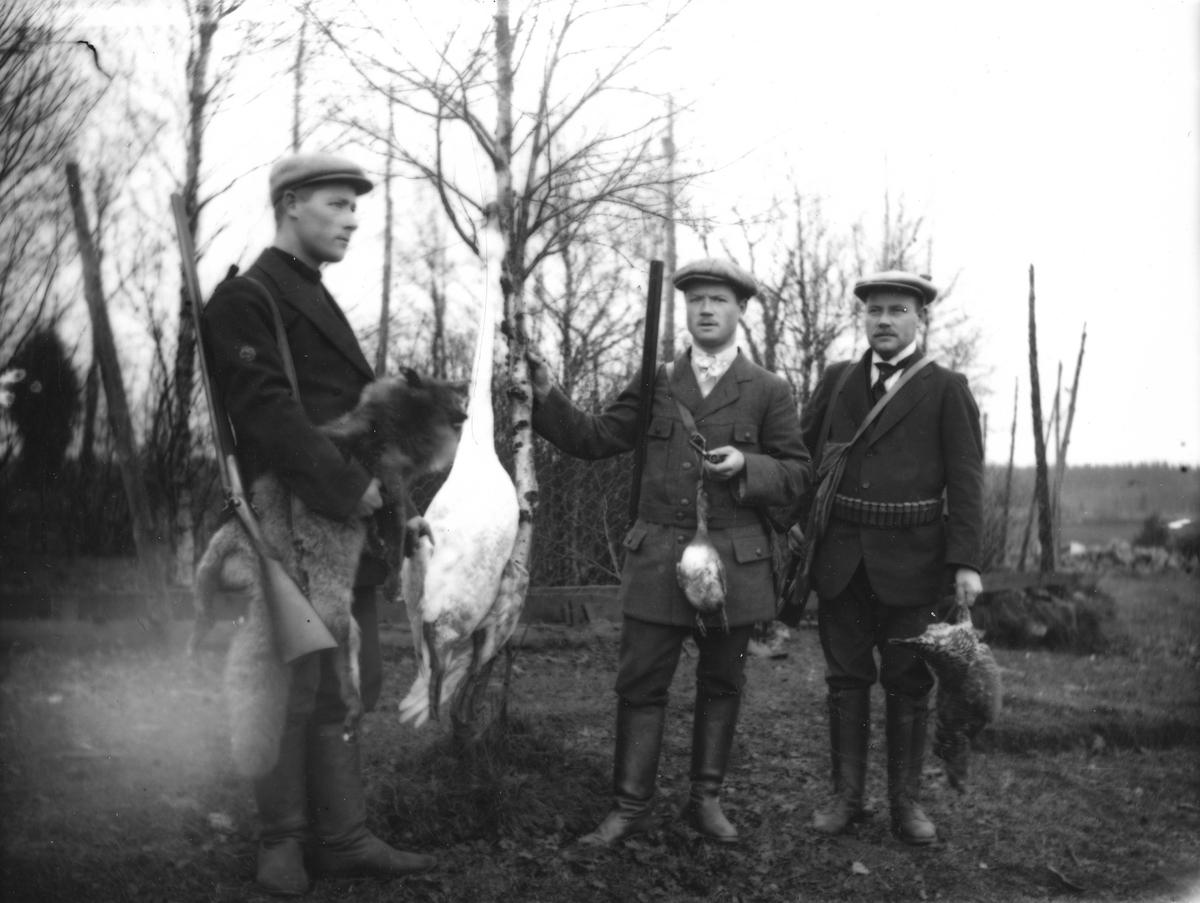 Tre män poserar med hagelgevär och jaktbyte i form av fåglar och en räv.