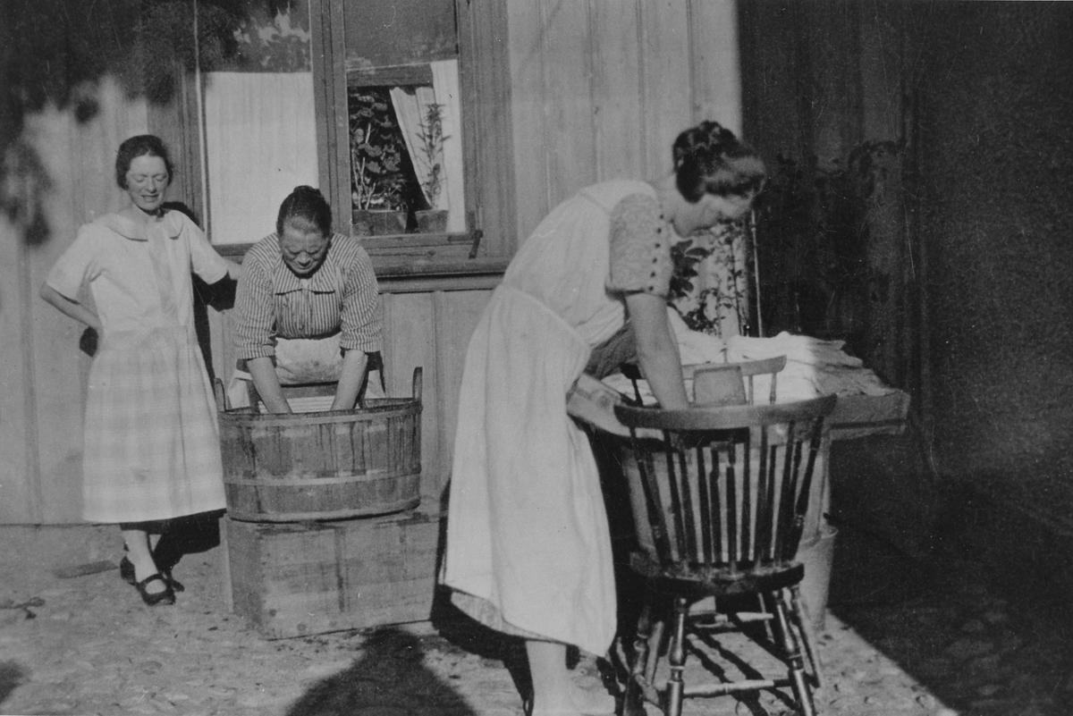 Tre kvinnor tvättar på gården Solgatan 7. Kvinnan i mitten är Amanda Dahlgren som står med tvättbräda i en balja. De två andra kvinnorna är hennes döttrar.
