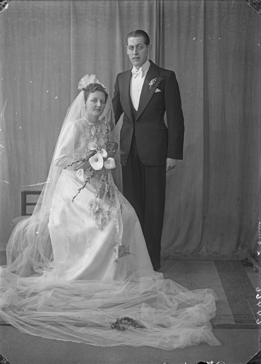 Portrett. Brudebilde. Ung kvinne i lys brudekjole med slør og ung mann i smoking med lys sløyfe. Brudepar. Bestilt av Johannes Ulveraker.
