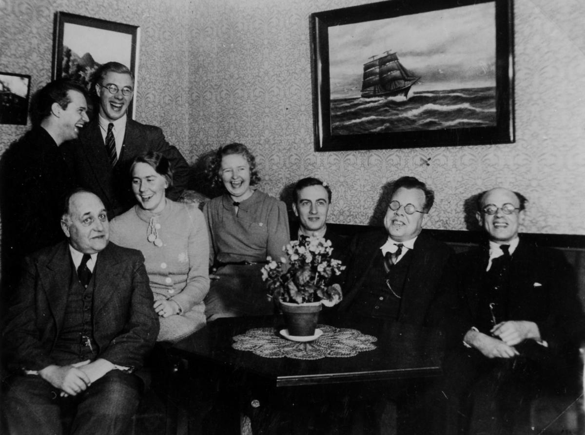 Gruppbild av 6 män och 2 kvinnor som skrattande trängs på en soffa. På väggen bakom dom hänger tavlor, där ena har motiv av ett skepp till havs.  Esperantoklubben i Alingsås. Mannen längst till höger är Erik Edholm.
