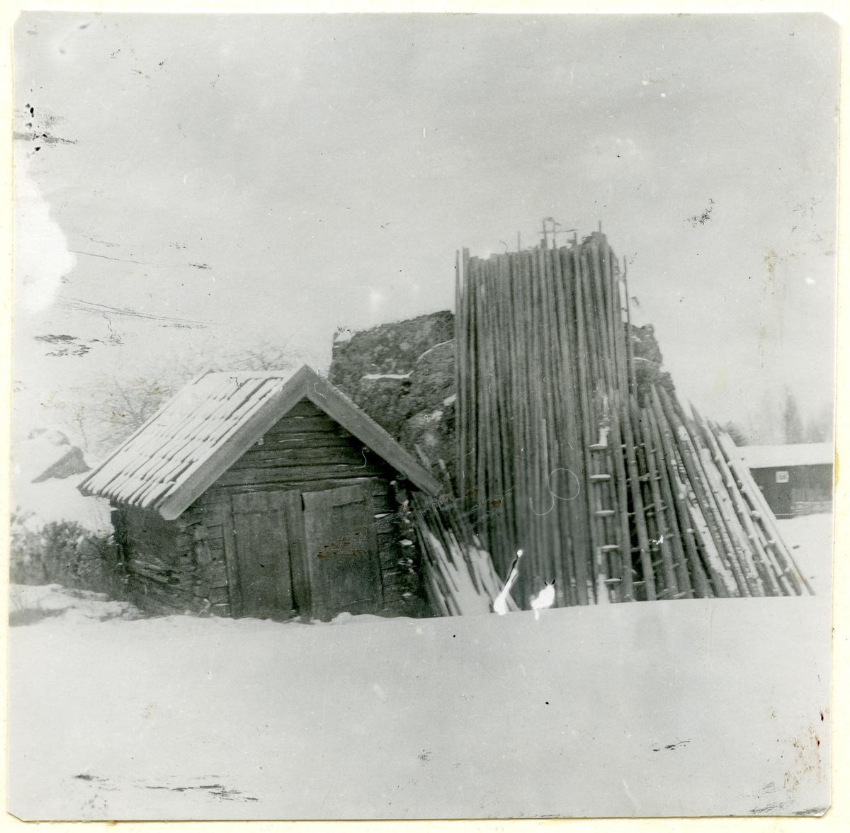 Fläckebo sn, Väster Vrenninge.  Sotarstugan. Liten stuga bredvid stor sten, där det står långa störar lutade.
