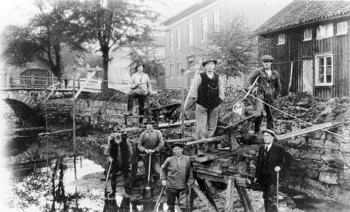 Sju män står i Lillån vid en träställning med spadar och verktyg i händerna vid upprensning av Lillån, vid Gasverksbron. Kv Hoppet mot Västra Ringgatan till höger och kv Solen bortanför.