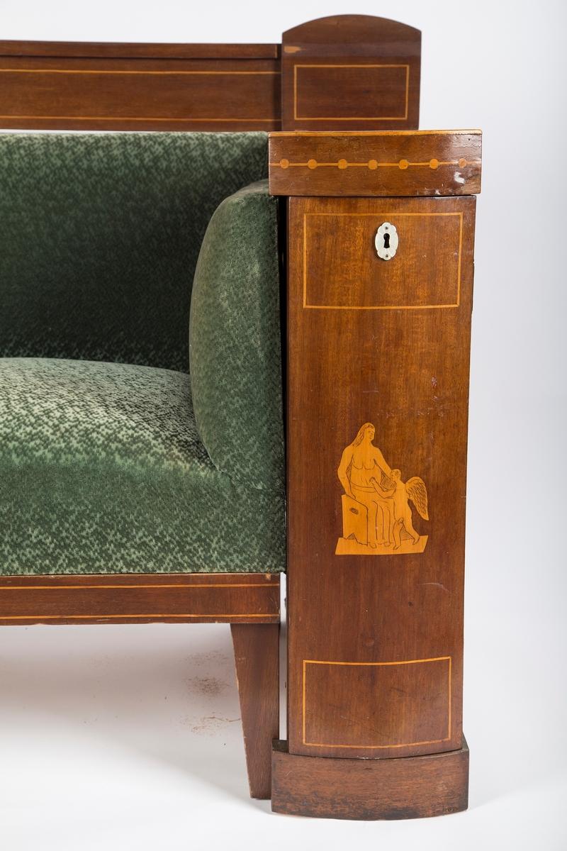 Sen-empire møblemenet bestående av skapsofa, fire armstoler og et rundt bord.  Skapsofa med forhøyet rygg og to skap. Sofa trukket i grønn plysj, overstoppet rygg og sete. List nede ved bena dekoreret med intarsia. På sofaens venstre side er det festet en treplate på yttersiden av armlenet. På høyre side er det trukket et stoff på yttersiden av armlenet, Sofaens treverk er synlig på baksiden. Den forhøyede ryggen har et kvadratisk trestykke med buet overdel i hver ende. På undersiden av disse er det plugger som brukes til å feste den forhøyde ryggen til sofaens skap. Trestykket på høyre side mangler en list. På baksiden av den forhøyede ryggen er det en rekke spiker og rester etter tråd og tekstil. Sofaens skap har skapdør med buet front og tydelig antikk-inspirert intarsia. Samme motiv som på stolene, men ser ikke ut til å være samme kunstner. Innvendig er det en hylle. Hvert skap har et nøkkelhull som er dekorert med perlemor, men nøkkel mangler. På oversiden av skapenene er det borret hull for feste av sofaens forhøyede rygg. Det er borret ett hull i venstre skap, og to hull i høyre skap. Det er også borret hull i skapsidene som vender mot sofaen. Skapenes bakside har spiker med tekstilrester.  Fire stoler med armlener. Armlenene er mørkere enn stolene. Trukket og stoppet sete. Svakt buede bakbein. Intarsia i tverrstykke og ryggbrett, klassiske figurmotiv og fabeldyr. Antikk-inspirert. Samme motiv på alle stolene, men med små ulikheter. Enkel intarsia i de to fremste stolbenene, rutemønster, og en stripe i listen under stolsetet. Stolene har noen skader, stol B har fått armlenet slått av, mens stol C har et armlene som er løst oppe på grunn av en manglende skrue. Stol D har et armlene som er festet til stolen med tråd øverst, og sokkelen ser ut til å være limt på.  Bord med rund bordplate og firkantet underhylle. Sarget er felt inn i de fire bordbena, og bordplaten er festet til sarget med 12 klosser.  Det er skjært ut en spalte i midten av hvert bordbein, bred ø
