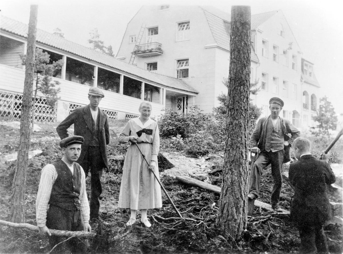 4 män och en kvinna arbetar, på en sluttning, runt ett träd. Bakom dom syns Bolltorps sanatorium med tillhörande veranda.