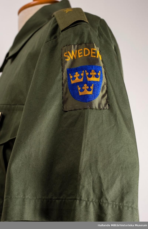 Skjorta m/87-93. M7320-034000.  Grön skjorta, kortärmad med mjuk, nedvikt krage. Fasta axelklaffar med hylsor, gradbeteckning för major. Skjortan har två bröstfickor, utanpåliggande med veck och knäppbara lock. På vänster bröstficka finns en namnskylt. På vänster skjortärm, nationalitetsmärket för Sverige. På höger skjortärm, FN-märke (United Nations) samt Nordbat2-märke. Storlek 43.