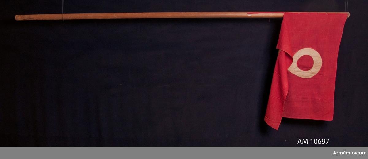 Grupp B. Duk av rött bomullstyg med en vit 2:a utförd i applikation på båda sidor. Duken är ej virad runt stången innan spikning. Brun stång, möjligen avkortad. Spets och doppsko saknas.  2 kompaniet.