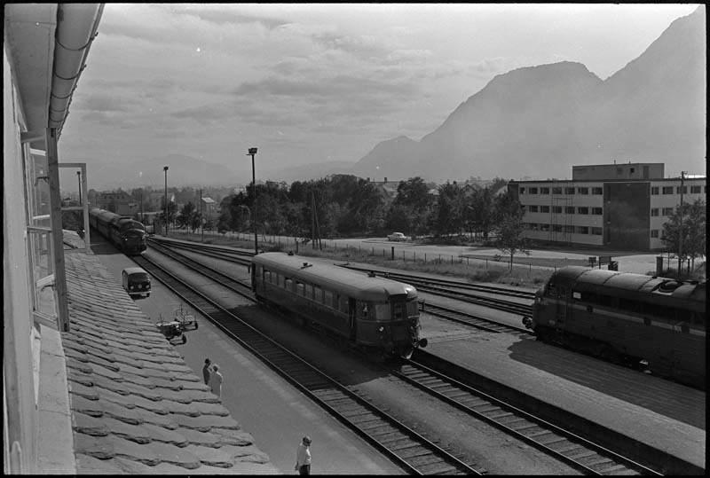 Torvet i Mosjøen 11.mars 1971. Biler er parkert både på torvet og i Strandgata. Jernbanestasjonen. Aluminiumsverket.