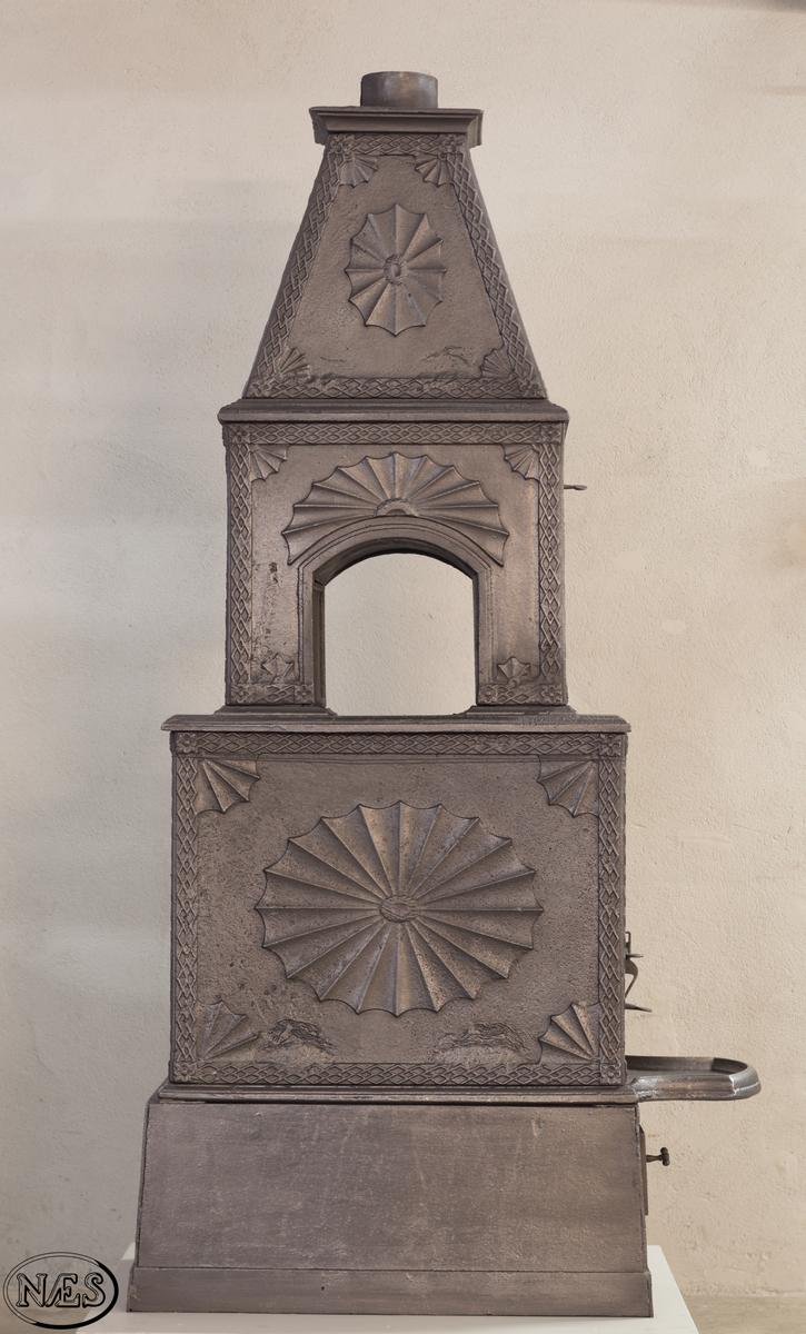 To etasjes ovn med pyramidetopp. Platene er dekorert med vifteformede rundinger og deler av slike. Innrammet av rhombebord.