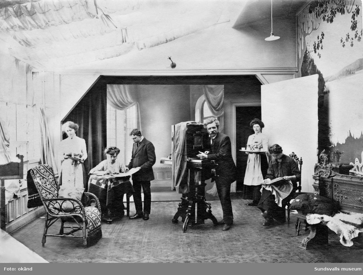 Fotografen A. E. Waagsböe stående vid sin kamera i sin fotoateljé på Storgatan 12-14 i Sundsvall. Adele Kindlund var innehavare till ateljén före Waagsböe. Bild 2 är ett vykort med samma motiv men i beskuret format.