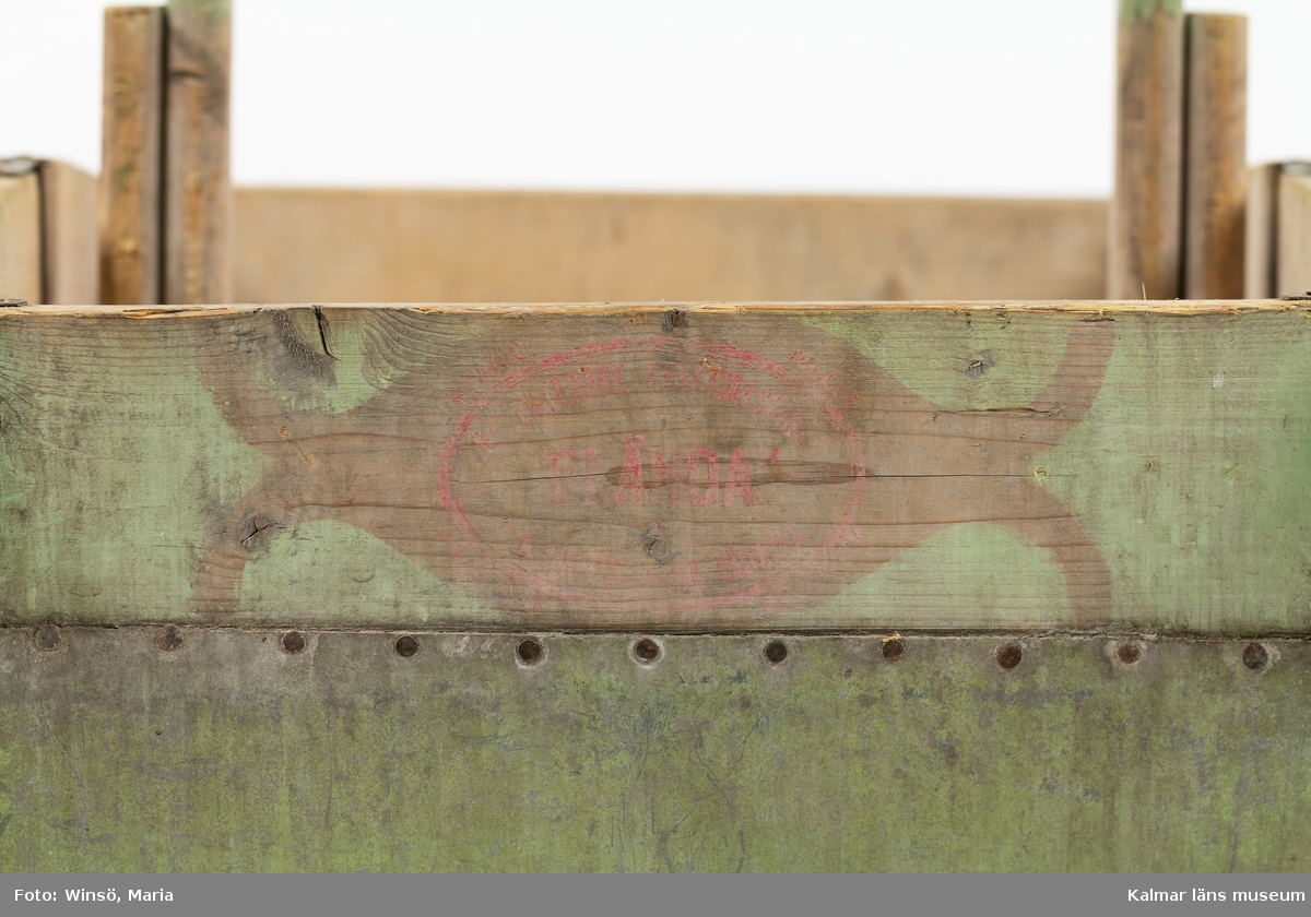 """KLM 46215. Tvättvagga. Av trä och metall. Halvmåneformad grönmålad behållare som undertill är klädd med plåt. Fyra ben. Tryckt text på båda kortsidorna, delvis svårläst. På ena sidan: PATENTERADE TVÄTTMASKINEN """"BLÄNDA"""" INDUSTRIFABRIKEN HÄLLABÄCK, STARK BILLIG PRAKTISK EFFEKTIV."""