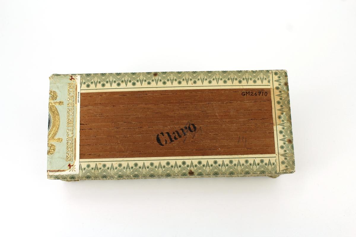 """Cigarrlåda av cederträ. Platt, rektangulär med pressad, ofärgad dekor på locket: """"P.C. RETTIG & Co GRUNDAD ÅR 1809 GEFLE"""" samt fabriksmärket (G över ankare). Tryckta, mönstrade pappersremsor längs kanterna samt påklistrade etiketter, varav en med texten """"MARQVIS"""" samt porträttmedaljong. Inuti lådan dekortryck på lock och skyddspapper. Tillverkad för P.C. Rettig & Co, Gävle."""
