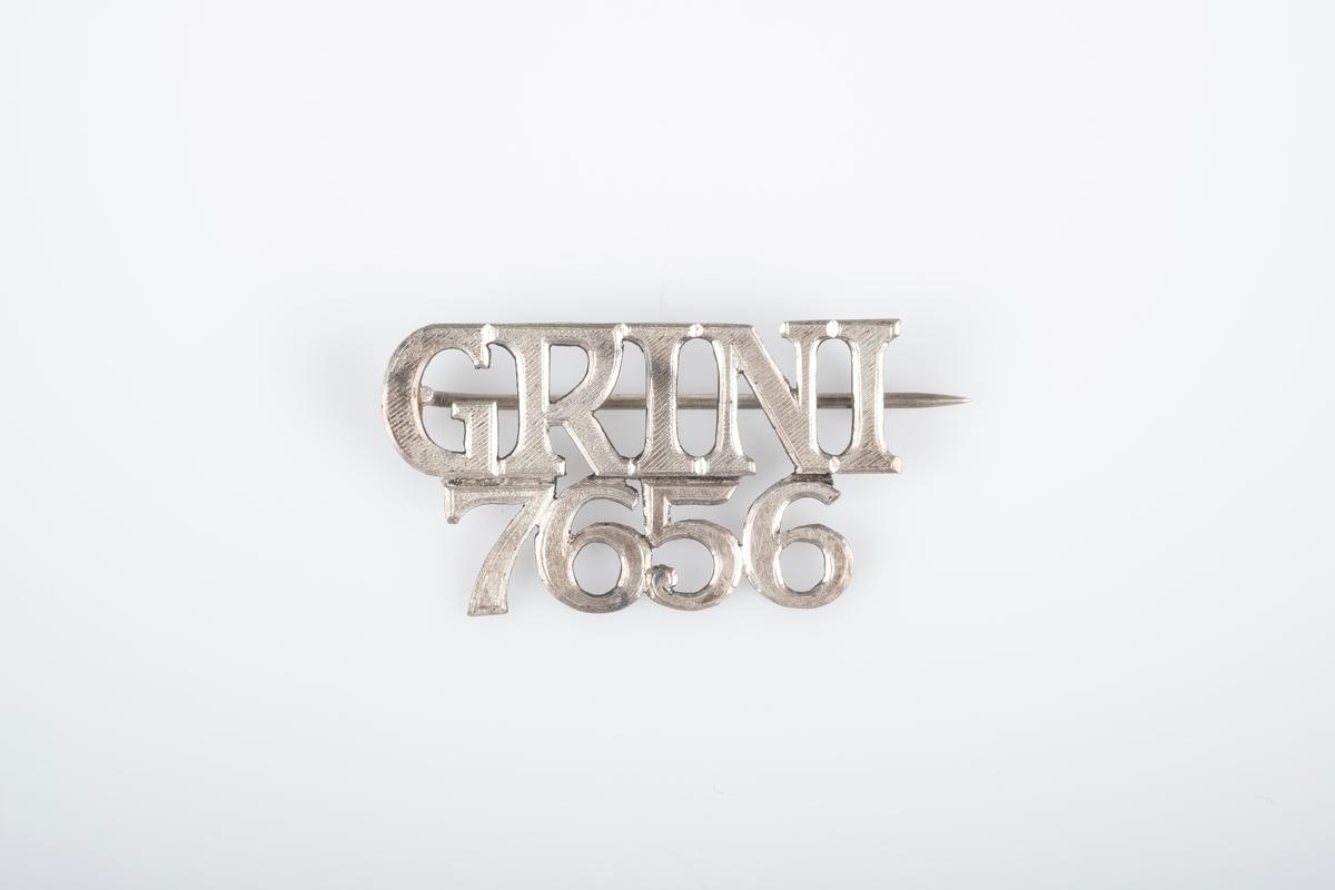 """En nål i metall med teksten """"Grini 7656"""". Nål bak som festes i en krok."""