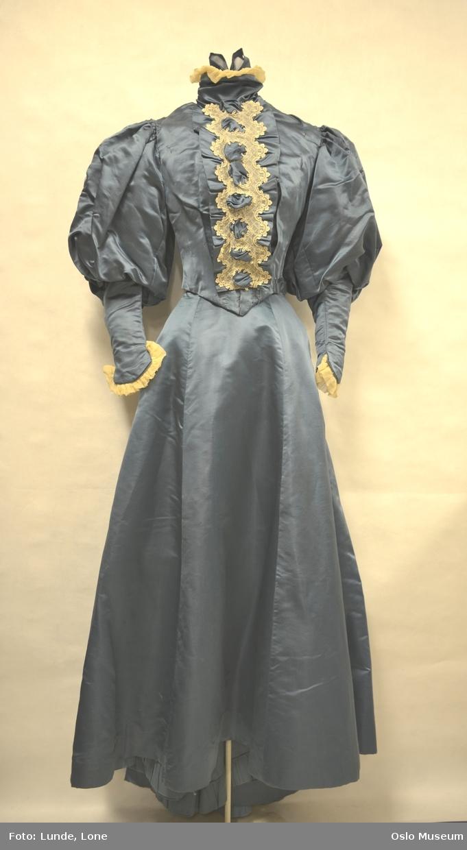 6bf5f5db Dueblå kjole i silkeduchesse. Ecrufarget blonde foran på liv og rynket  chiffon i erme og