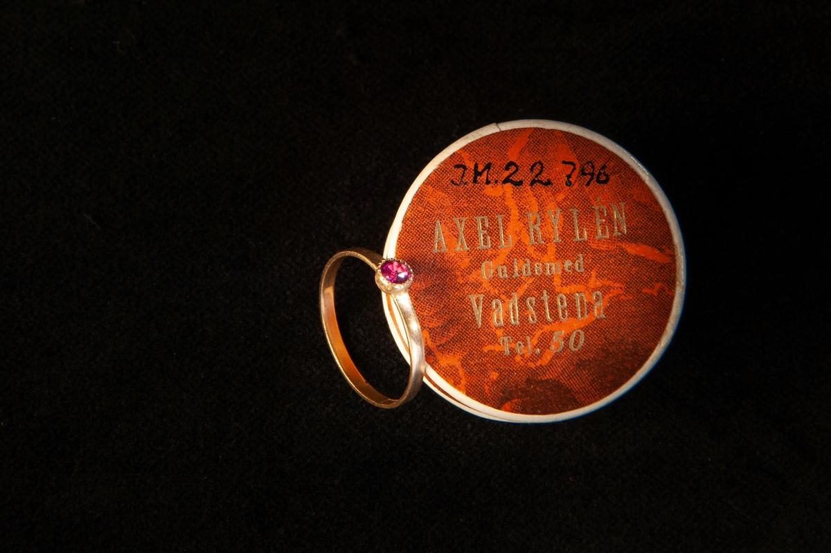 En smal guldring med infattad ljusröd sten (troligen simili (glas), möjligen rubin ?).  En tillhörande rund smyckesask i papp.