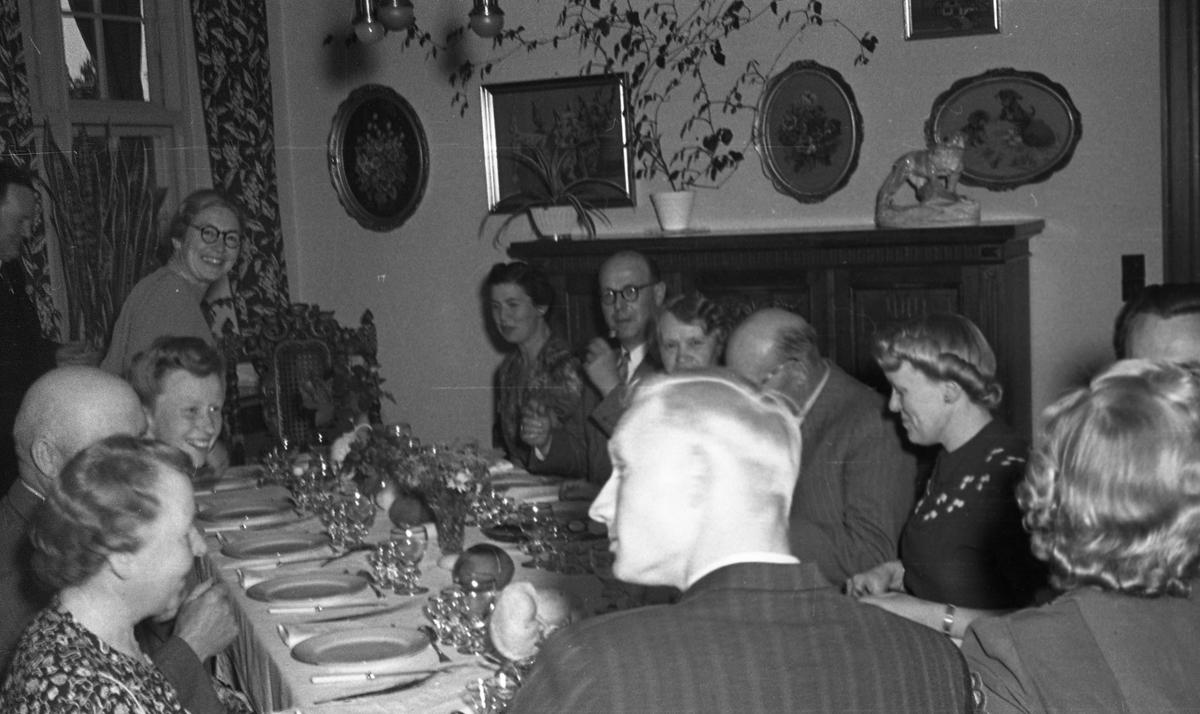 Middag. Gruppebilde med tretten personer. Seks menn og syv kvinner samlet rundt middagsbordet. Suderøy på vei til fangstfeltet.