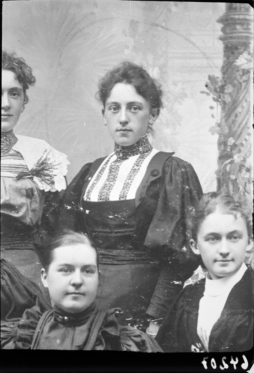 Gruppebilde. Gruppe på fire kvinner. Kopi av positivt foto. I senter sitter en ung mørkhåret kvinne med oppsatt hår i en mørk kjole med lys front med pynt. Bestilt av Ludvig Eriksen