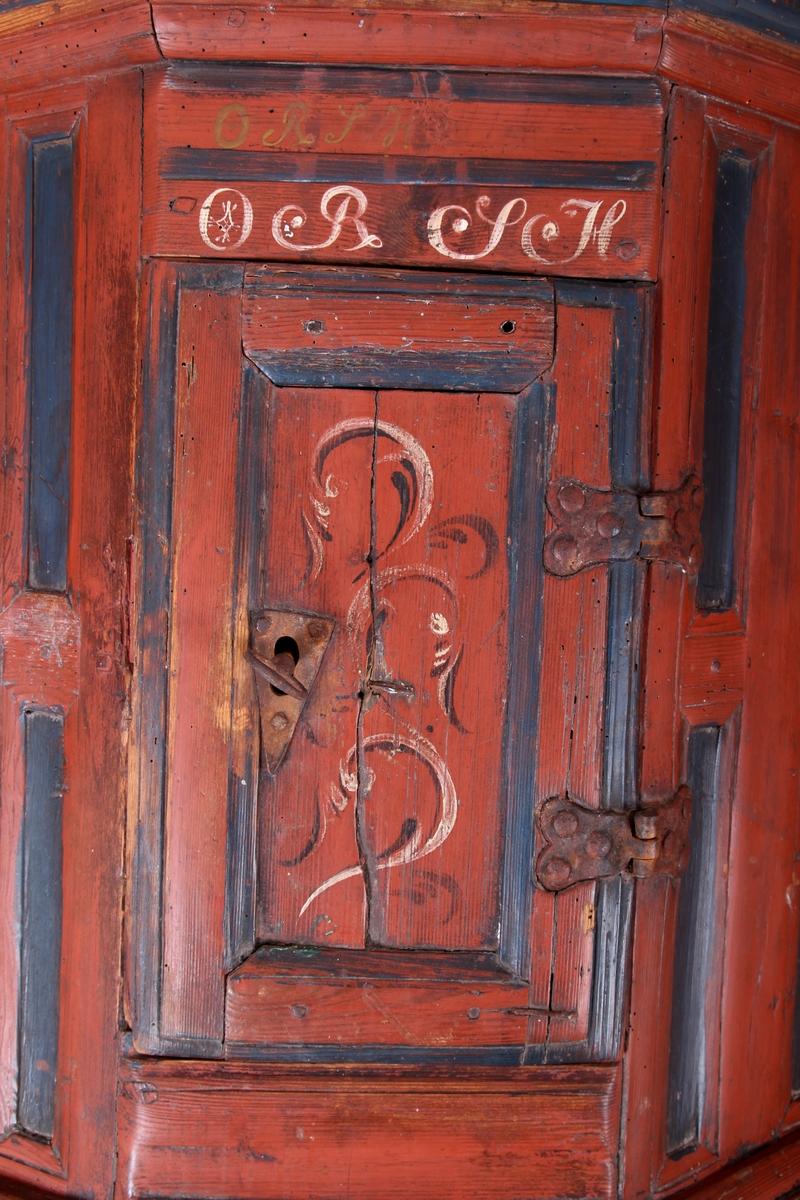 Rosemalt hjørneskap med dørskap og sidefelt med fyllinger. To hyller inni.