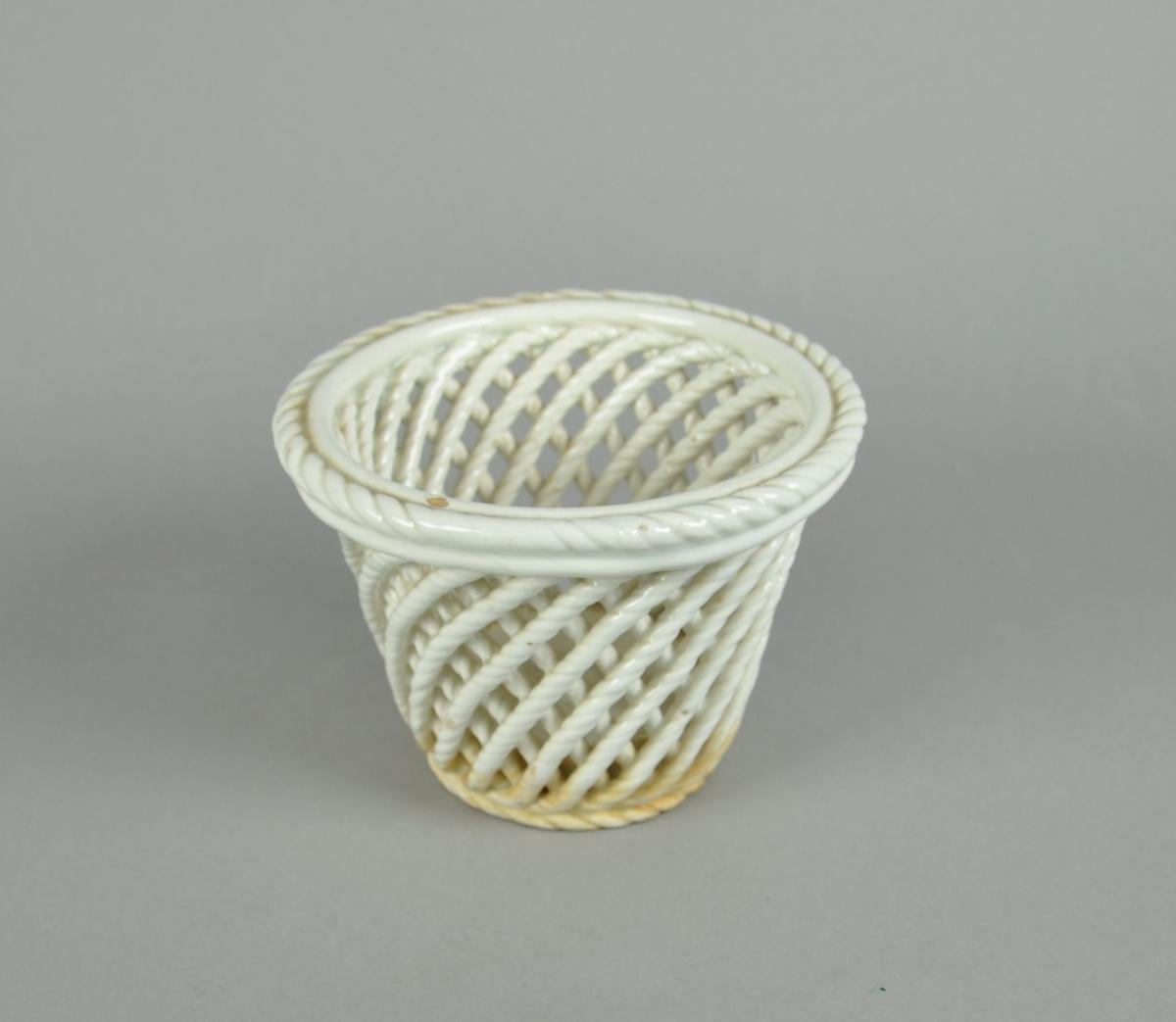 Hvit blomsterurne av glassert keramikk. Urnen har gjennombrutt, flettet form.