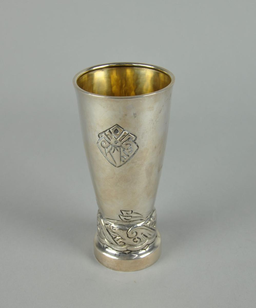 Pokal av sølv. Pokalen har sylindrisk form med sokkel nederst, og utvidelse mot toppen. Har inngravert og siselert dekor av en rekke fugler ved sokkelen, og krone med innskriften KNS under.