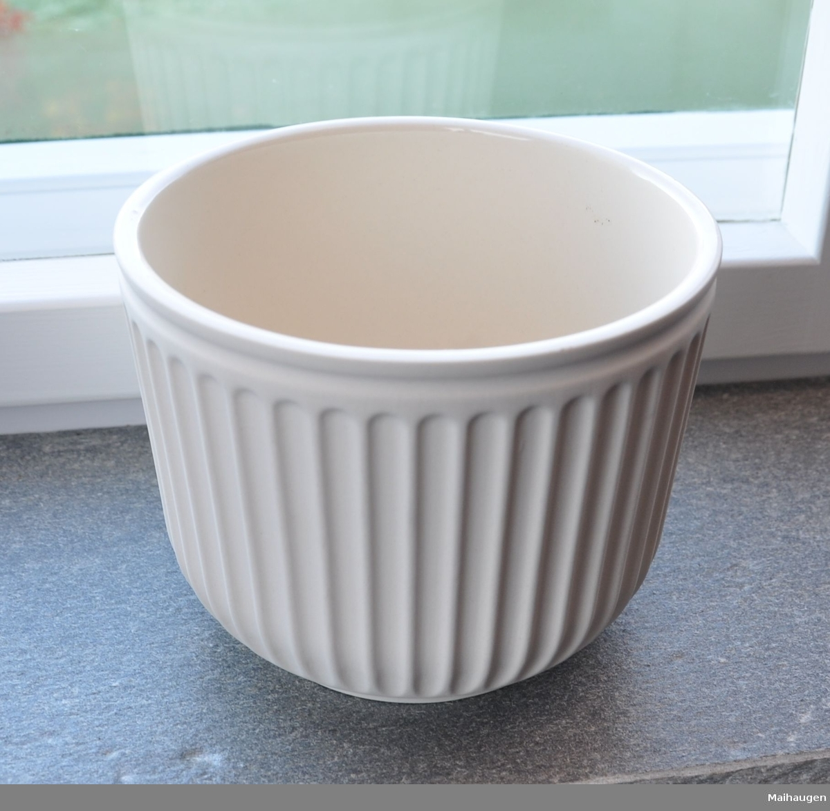 Potteskjuler av uglassert keramikk. Sylindrisk form med avfaset bunn og kannelert dekor på korpus.