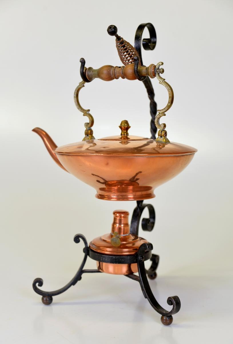 Tekök av koppar på ställning av järnsmide. Denna typ av tekök var i bruk under slutet av 1800-talet. Detta har troligtvis tillhört någon av familjerna Dickson i Göteborg.