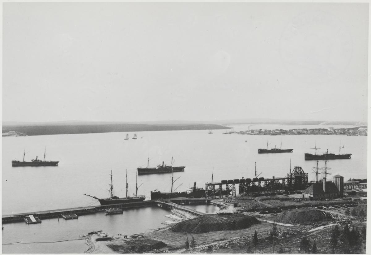 En del av lastageplatsen med elevatorn och maskinhus. Några malmångare väntar på att få inta last. I bakgrunden på udden syns en del av Luleå stad