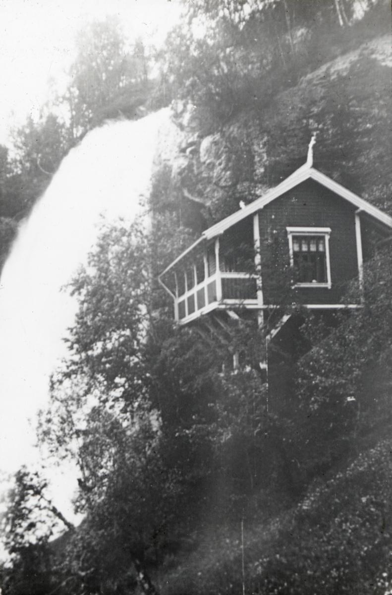 En liten hytte ligger i en bratt fjellskråning ved Steindalsfossen. ..Bildes tittel stammer fra påskrift på lysbilderammen av Anders Beer Wilse.