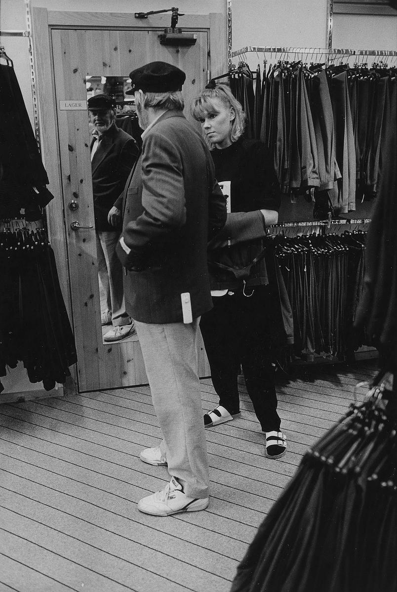 Ett butiksbiträde hjälper en man som provar en kavaj på Gulins Kungsgatan 31, kvarter Hjorten 19. I november 1990 flyttade butiken tillsammans med Lindex in i Epas gamla varuhus i kvarter Storken 12.