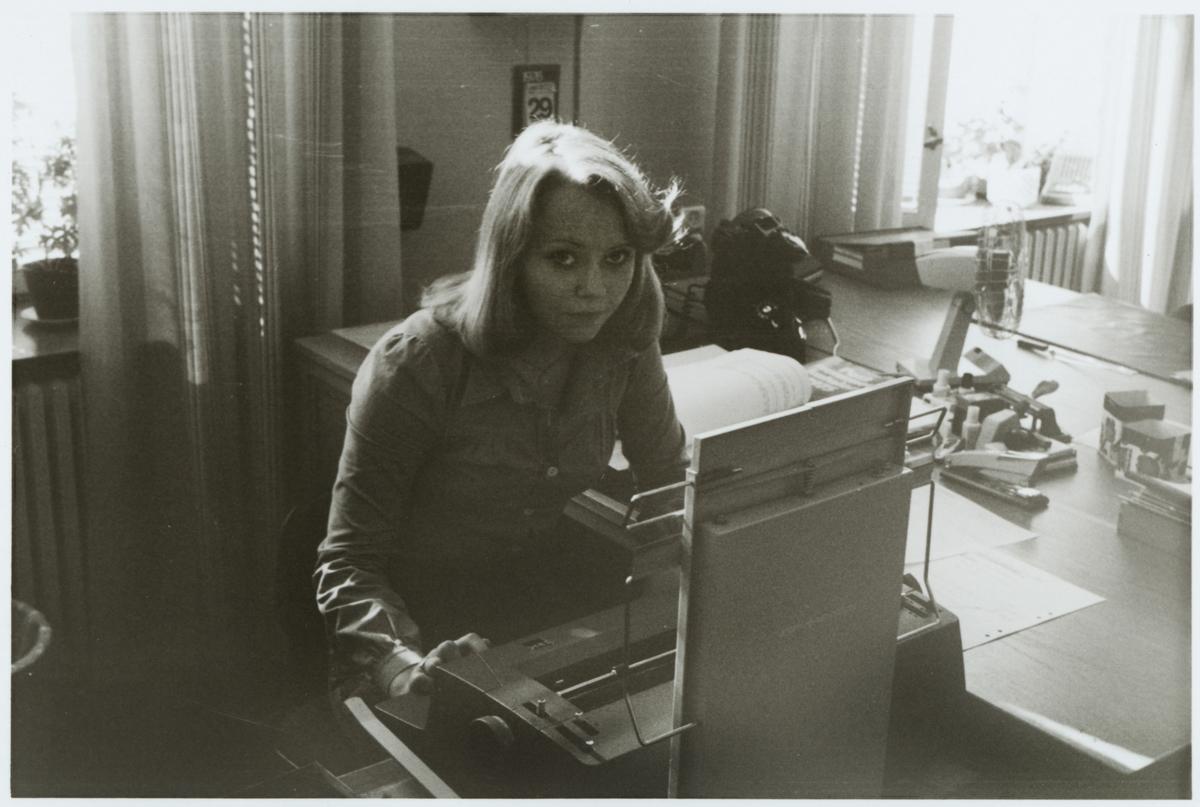 Marie Larsson vid en skrivmaskin på ett kontor.