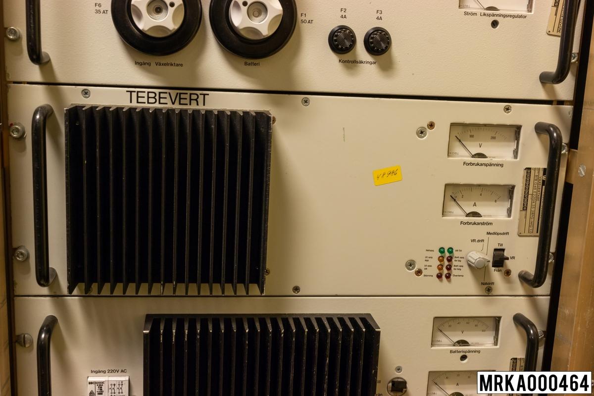 Likriktare. Strömförsörjningssystem 24 V, 48 V matas under normala drift med 220 V-växelspänning. Denna spänning likriktas, regleras och omvandlas till +24 V, -24 V och -48 V likspänning för strömförsörjning av sambands- och eldledningsutrustningar, nödbelysning samt underhållsladdning av ackumulatorbatterierna i ackumulatorlådorna. Vid spänningsfall matas strömförsörjningssystemet från ackumulatorbatterierna. Detta kan pågå under minst en halvtimma, sedan måste batterierna laddas om.  Övriga komponenter i strömförsörjningssystemet är likspänningsregulator, växelriktare, likriktare, likspänningsomvandlare och avstörningsfilter.  Ursprungsbenämning: LIKRIKTARE Ursprungsbeteckning: BTB E 230 G48/28 BW RU-PD