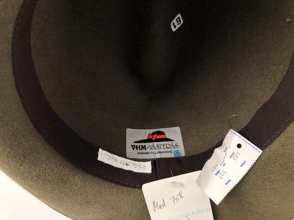 """Herrhatt av grön hårfilt (filt gjord av hår från hare). Monterad med ett brett ripsband och en rosett på vänster sida. Brunt foderband av ripsband, med fastnitad pappersetikett märkt: """"västerås HATT- och MÖSSFABRIK ab FORM 363 KVAL 307 GARN CM FÄRG 181, KOM 800. Inne i hatten klistrad vit etikett med en hatt samt märkt: """"VHM, VÄSTERÅS, SVENSK TILLVERKNING"""". Vidhängande etikett märkt: """"wigéns"""" och handskriven text """"Mod 758 Mont snusnäsduk (VHM 363), V1988"""". Inuti hatten finns även klisteretikett märkt """"61""""."""