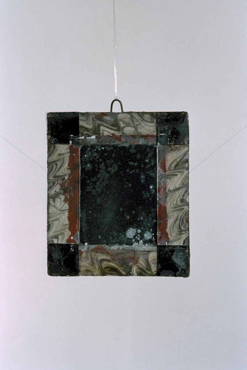 Liten, rektangulär spegel med ram av svartmålat trä samt påklistrade målade glasbitar. På två diagonala hörn har glaset spruckit och delar fallit av.