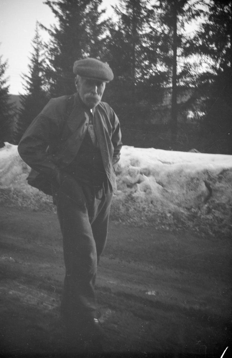 Portrett av eldre mann som går langs landevegen