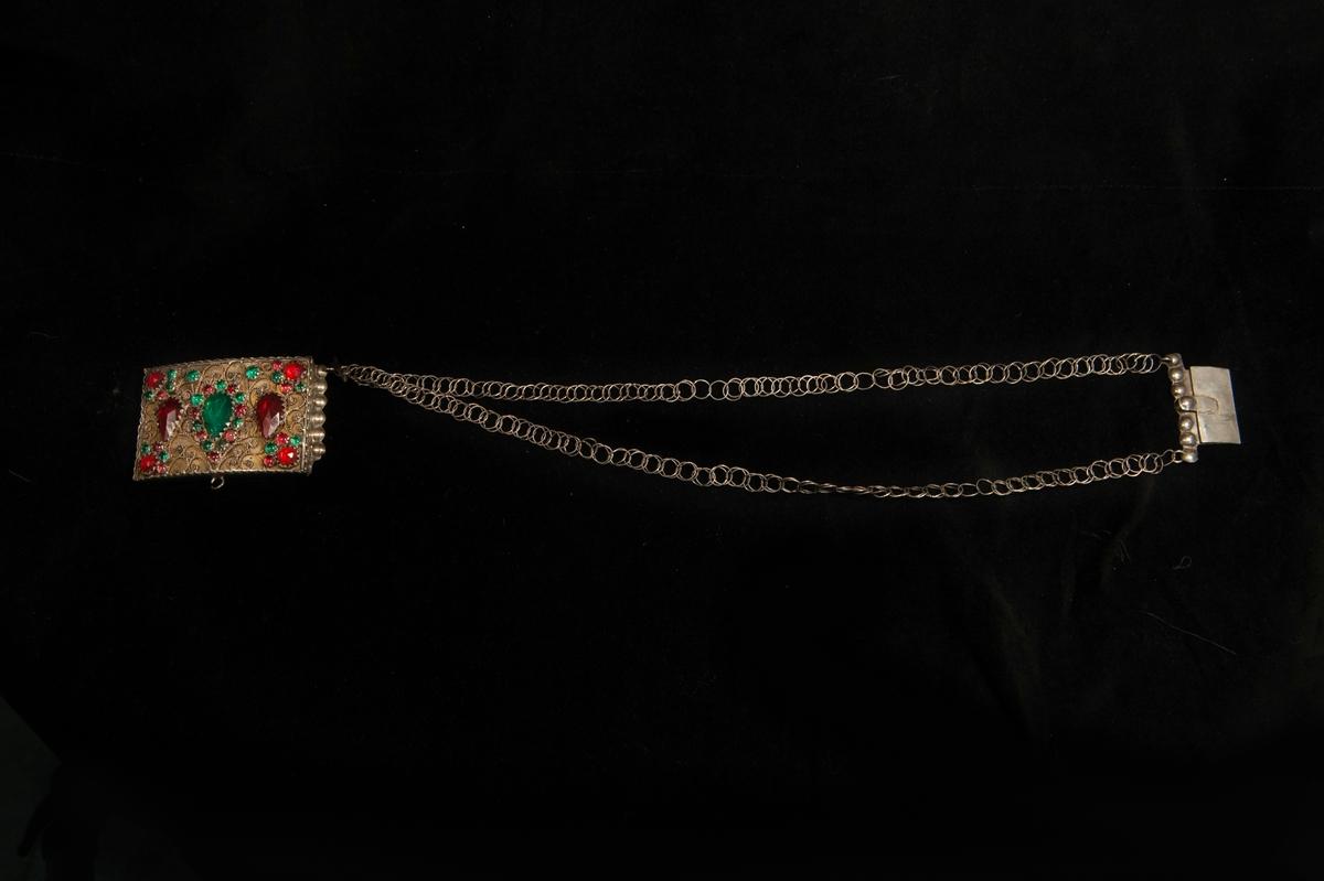 Ett halslås av silver med två enkla kedjor. Fronten prydd med filigranarbete med infattade, slipade glasstenar i rött och grönt. Undertill liten krok för hjärtformat hänge eller dyllikt.