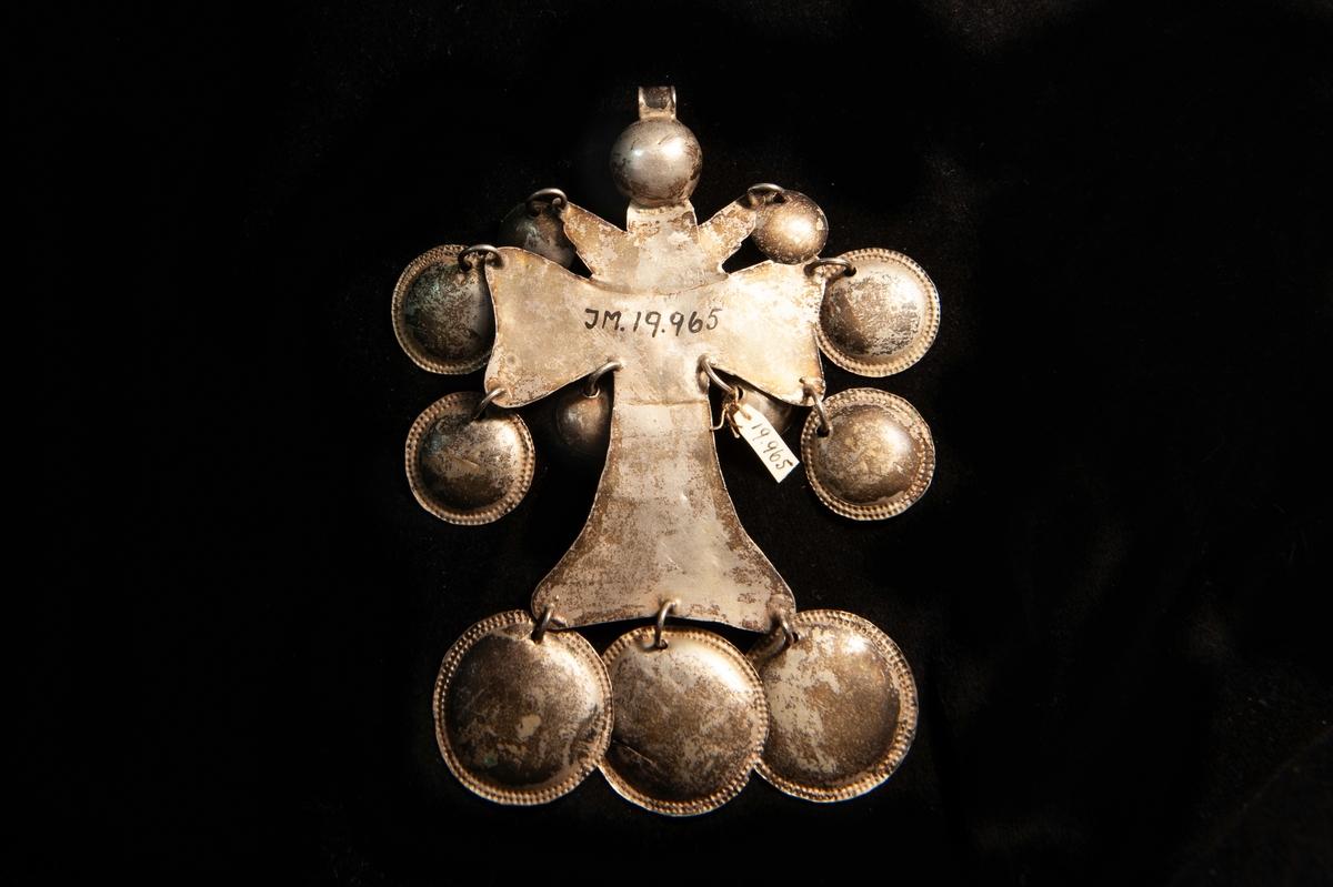 """Ett striglakors i ciselerat och förgyllt silver. Motiv i form av Jesus på korsetmed ett naivt änglahuvud ovanför. Behängt med 11 runda, små plattor (""""skålar"""") av ciselerat och förgyllt silver. Delvis otydliga stämplar."""