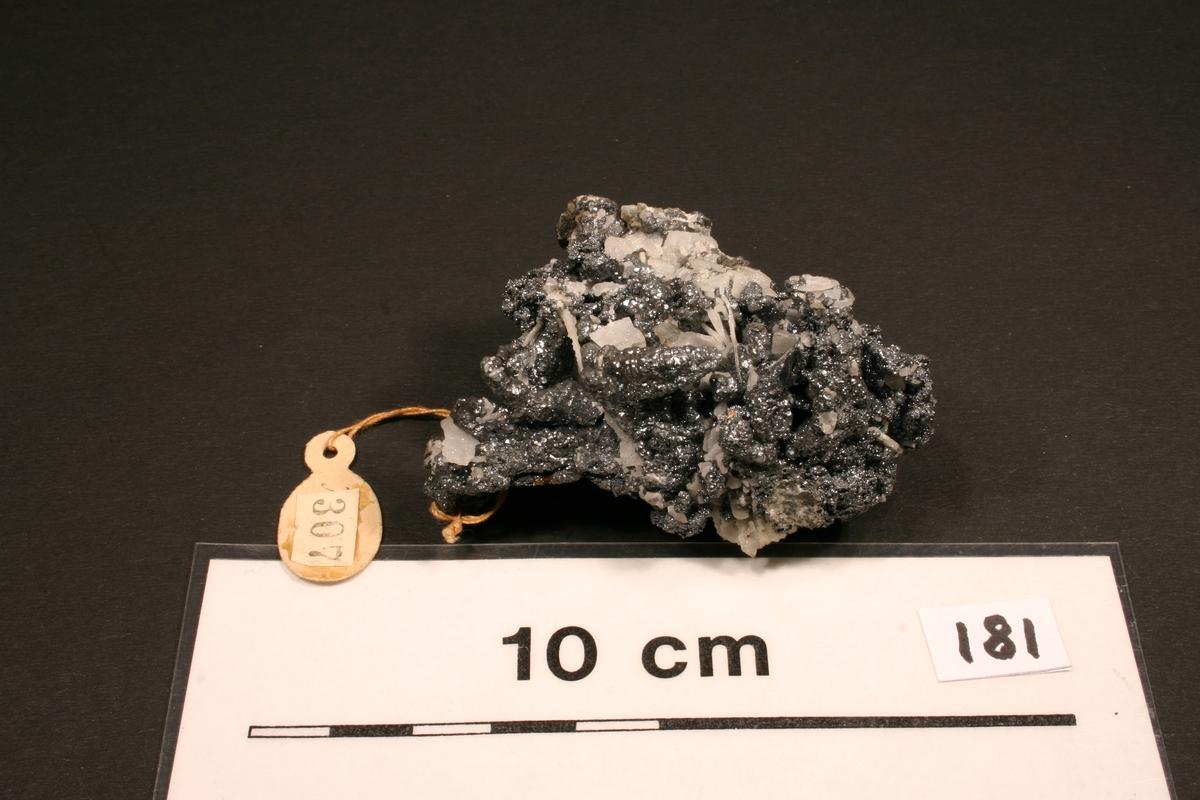 """Argentitt på trådsølv Etikett i tråd: 307, 1928 Vekt 121,40 Størrelse: 6,5 x 4,3 x 4,3 cm  Antagelig nr. 38 på innrammet plakat: """"38. Katalognr. 307, vekt 127 g (brutto), 100 g (sølvinnhold), G. Hülfe. Tråder av krystallinsk sølvglans med indre kjerne av gedigen sølvtråd - sulfidert."""""""