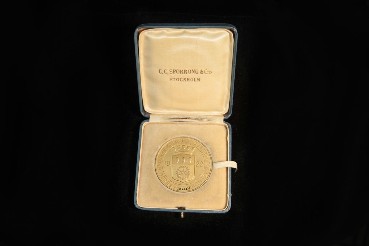 """En medalj av förgylld silver. På åtsidan Nässjö kommunvapen under en krona. Text runtomkring """"Nässjö hantverks- och industriutställning 1922"""". Frånsidan, inom en krans med lagerblad, en hammare på städd och kugghjul, samt texten A/B John löfquists skomanufaktur, Jönköping. Stämplar på kortsidan. Ligger i en ask klädd med blått papper. Insidan klädd med siden och sammet. Text på insidan av locket C.C. Sporrong & C:o Stockholm."""