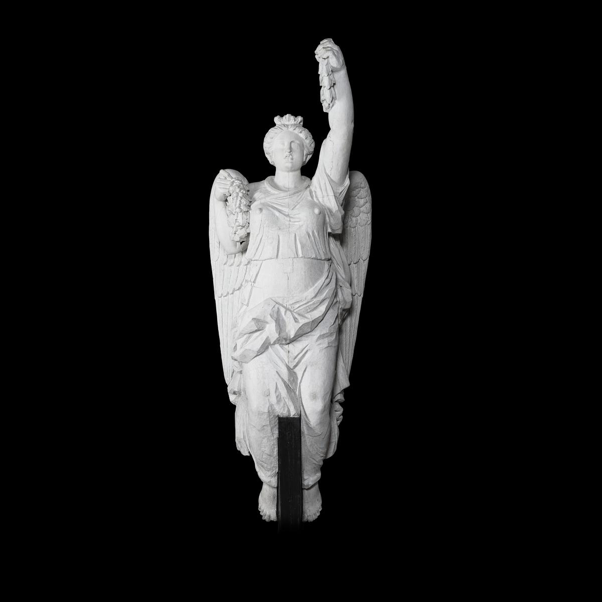 Galjonsbild tillhörande linjeskeppet Karl XIII. Betvingad och draperad kvinnofigur hållande lagerkrans i utsträckt vänster hand och krans av eklöv i höger hand intill höger axel. Sannolikt föreställande segergudinna. Färg: Vit.