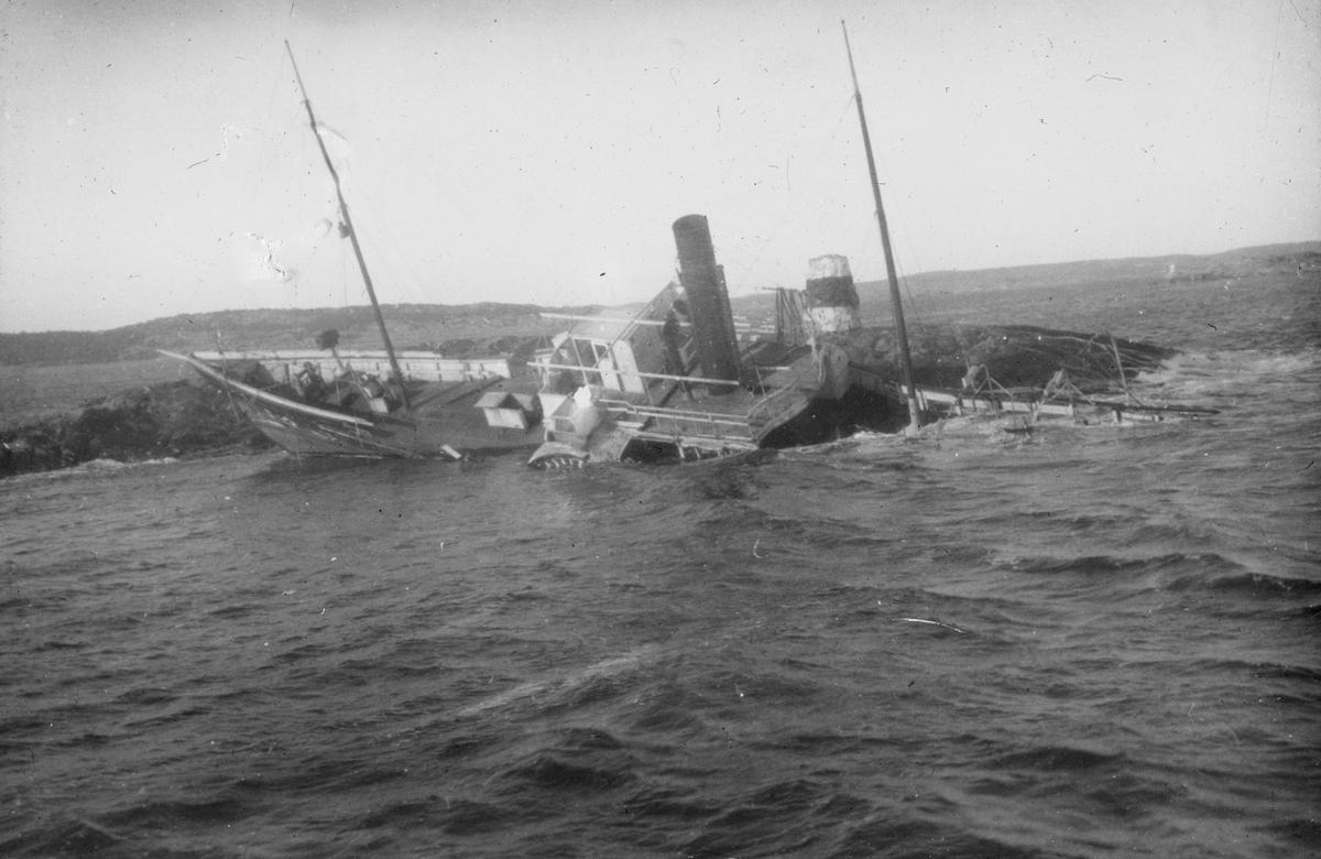 Dampskip med skovelhjul som har gått på land på en holme med sjømerke. Akterdekket ligger under vann.