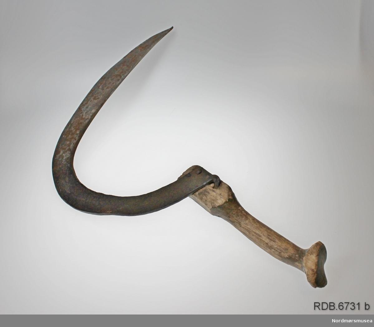 Hjemmesmidd sigd med treskaft. Halvmåneformet blad. I enden på sigdbladet er det laget en krok som er hamret inn i og festet til skaftet med en jernspiker.