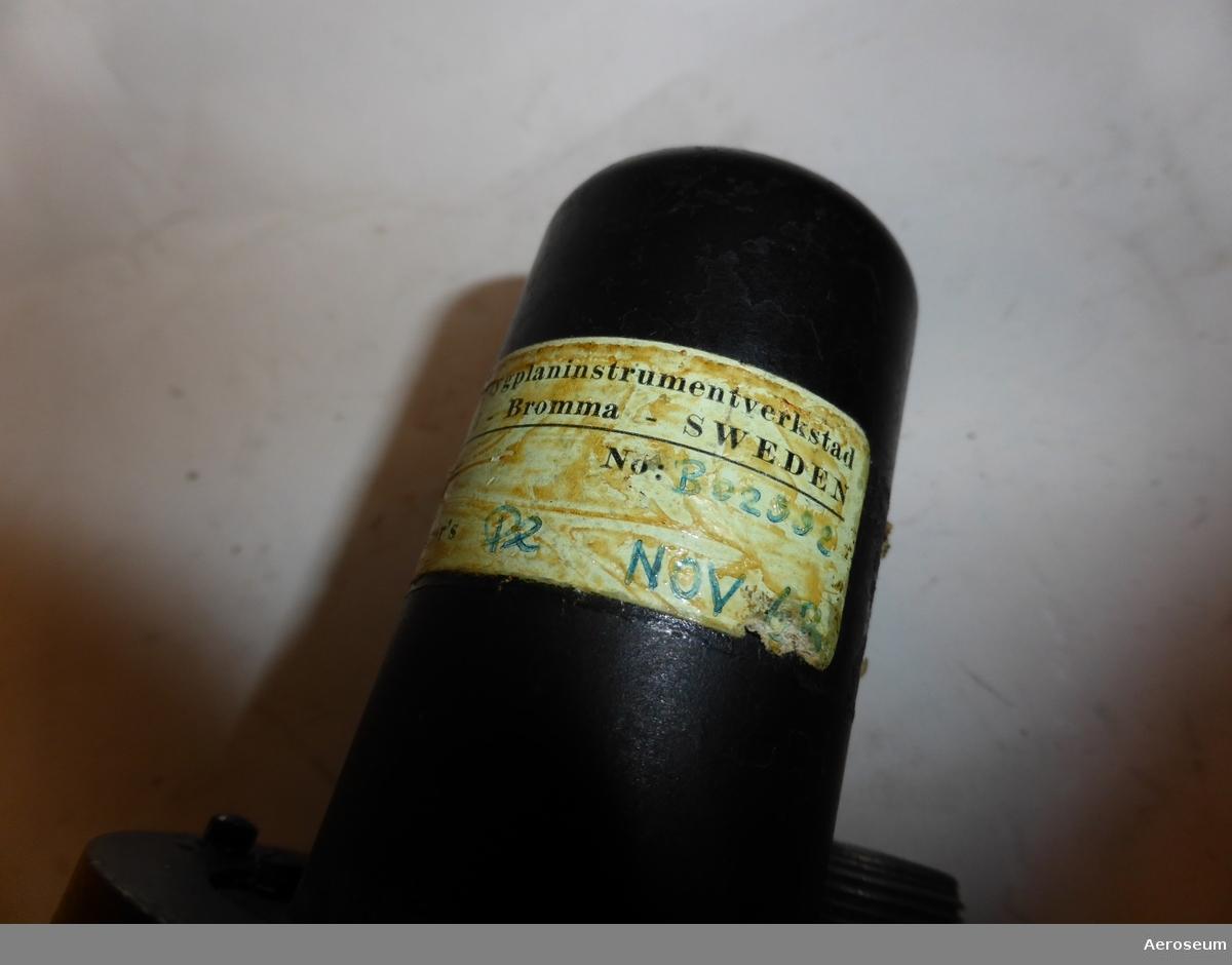 """Gyrohorisont, tillverkad av Sperry Gyroscope Co. och är gjord i svart metall. På föremålet står det skrivet i gul text (ganska utsuddat): """"JUN 19 1932"""". Det finns en trasig påtejpad ettikett där det står """"CA [går inte att tyda]SO C4 [går inte att tyda].A.[går inte att tyda] SPEC. AS396"""". I botten finns det en ettikett där det står: """"115 VOLTS [går inte att tyda]  CYCLES PART NO. 608588 - 2 - 13 SERIES NO. 2329B SPERRY GYROSCOPE CO. DIV. OF SPERRY RAND CORP. GREAT NECK N. Y. PATENT NO'S 2,409,659 - 2,452,473 - 2,485,552 OTHER PATENTS PENDING"""".  Det finns även en tejp där det står: """"[trasig tejp] HNISCH Flygplansinstrumentverkstad [går inte att tyda]platsinfarten 6 - Bromma - SWEDEN [går inte att tyda] No: B02002 [går inte att tyda]PAIR [bortrivet, men troligtvis CON]NTROL Inspector's Pe NOV 63"""""""