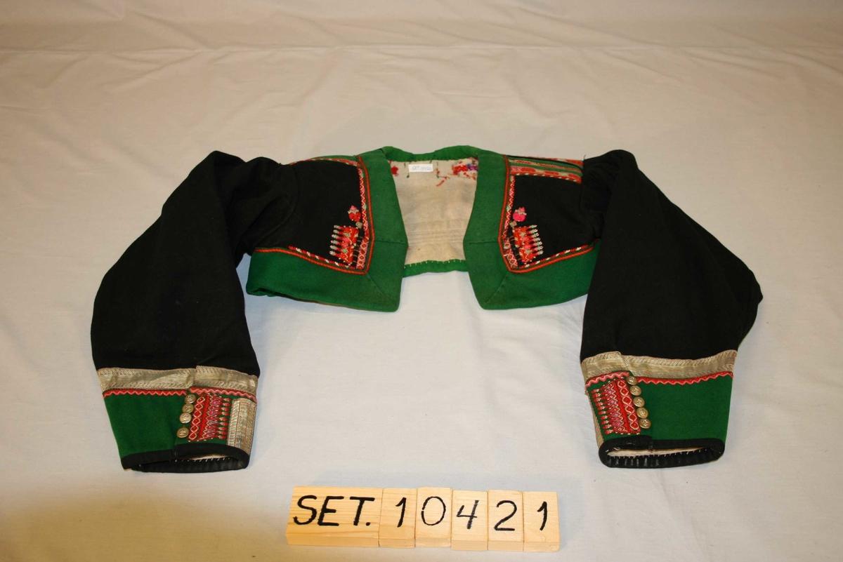 Stutt jakke med lange ermar, broderi og sølvborder, messingknappar på mansjettane.
